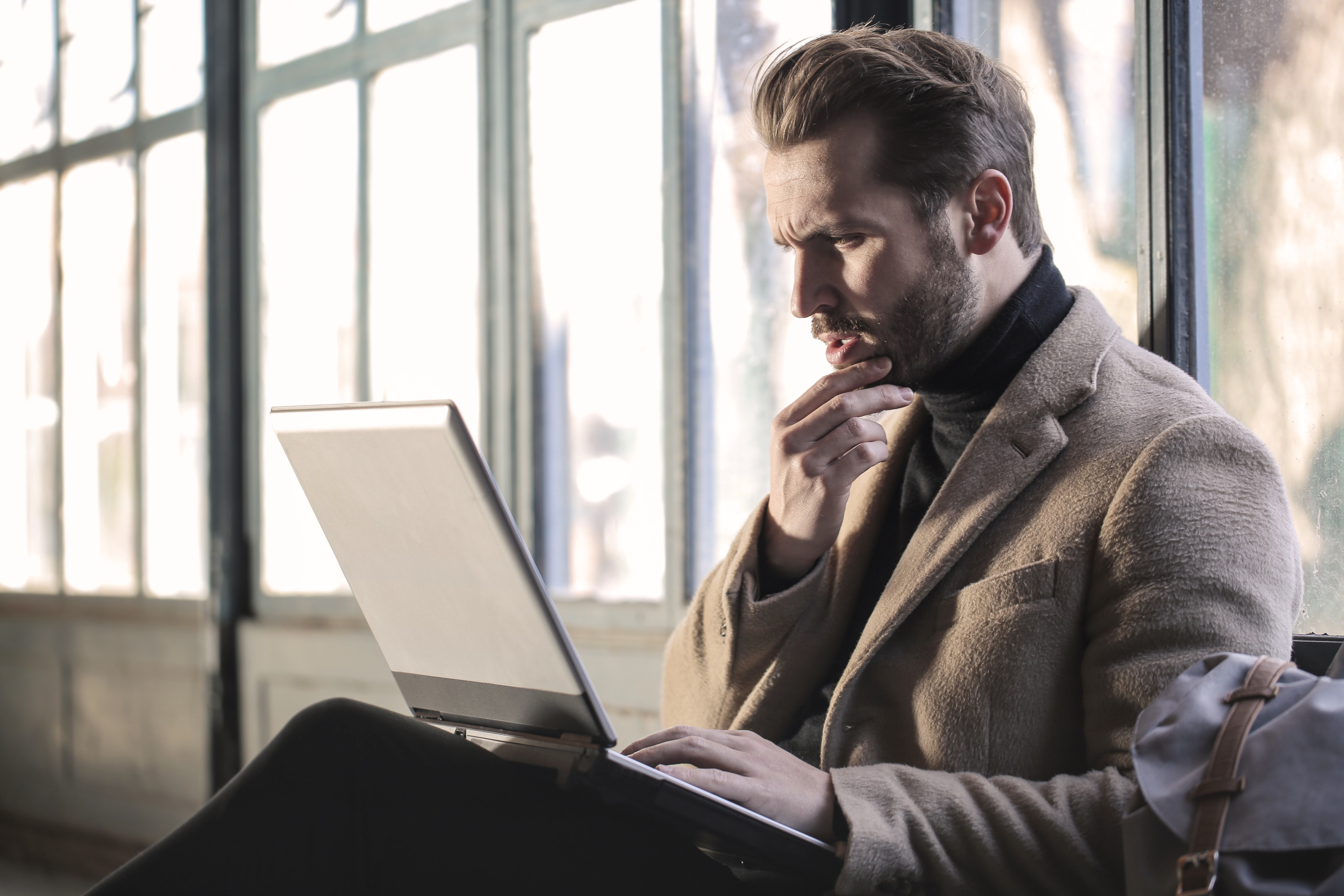 Alt-text: A man searching the net on how to write a good KSA narrative statement.