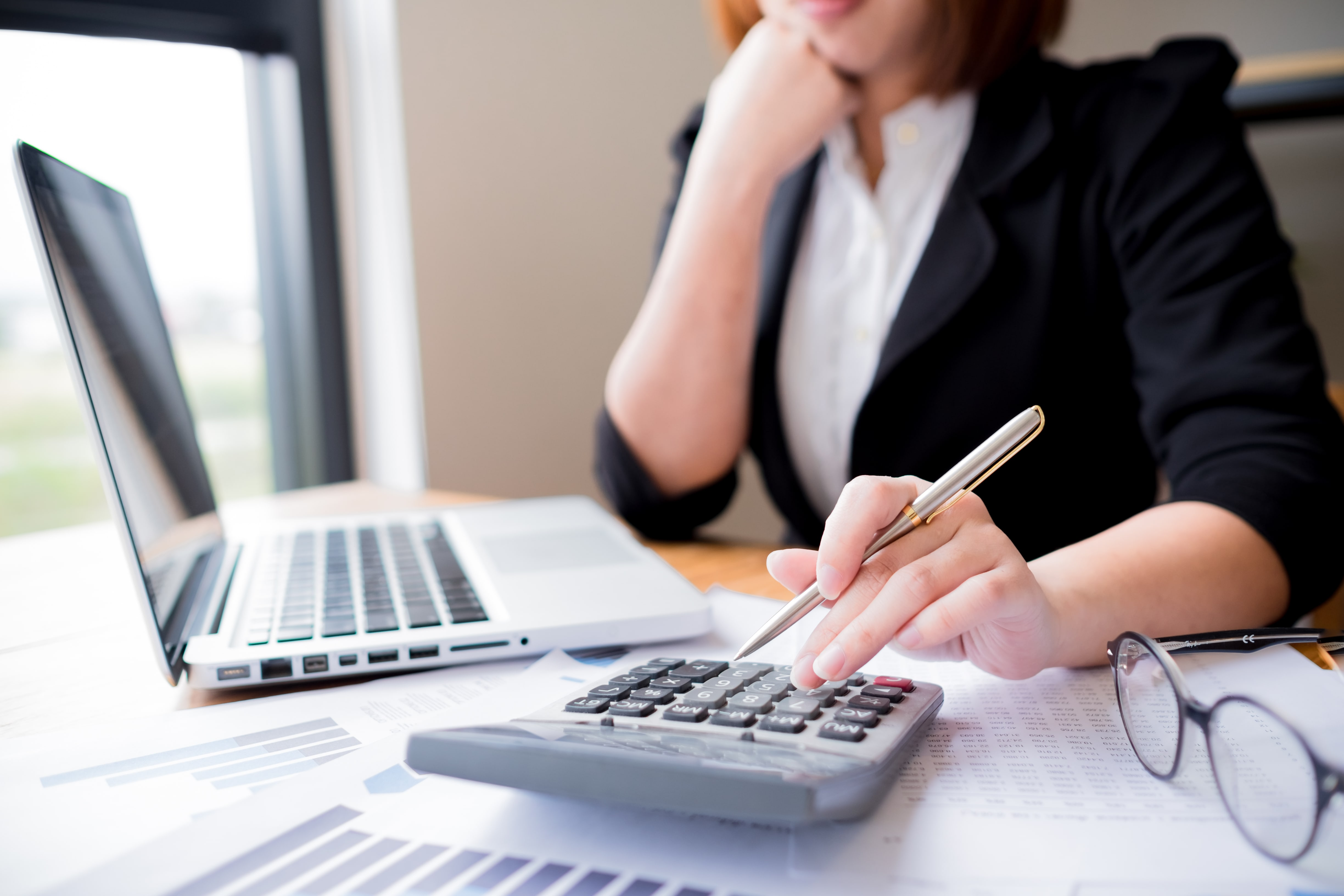 A female accountant viewing chief accounting officer resume examples on her laptop while using the calculator