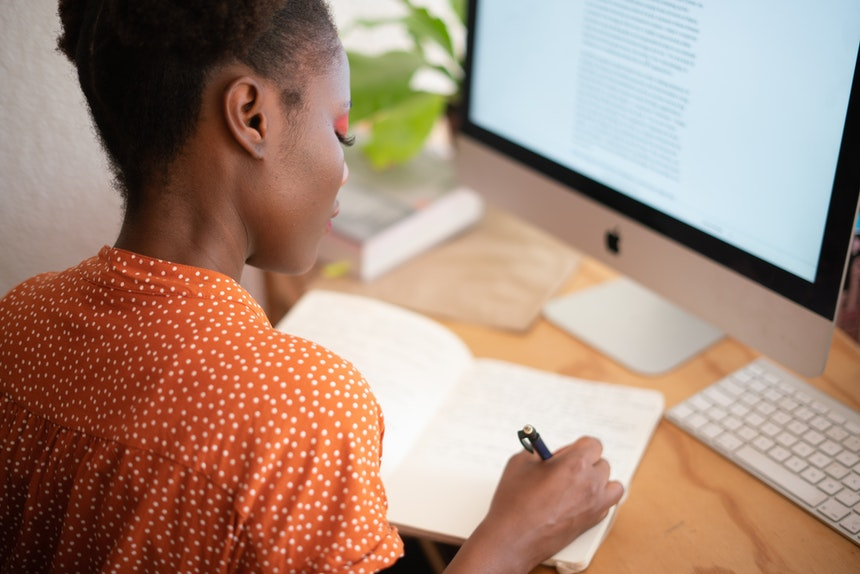 Woman writing job search tips while looking for cheap resume writing services on her PC